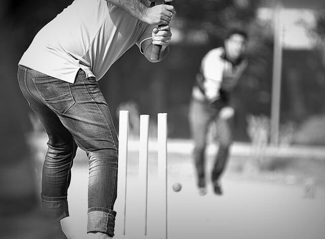 Man hitting a ball with a cricket bat